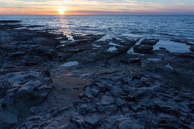 Sole che tramonta sulla riva con formazioni rocciose nel mare adriatico a savudrija, istria, croazia