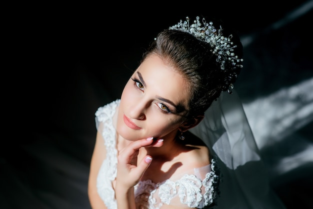 Sun and shadows play on the face of gorgeous bride sitting in the dark room