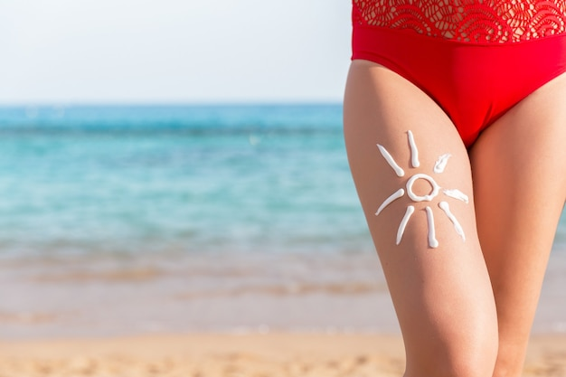 Sun shape is made of sunscreen on woman's leg at the sea background.