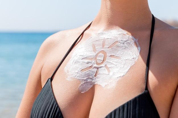 Солнцезащитный крем в форме солнца на женской груди на фоне моря.