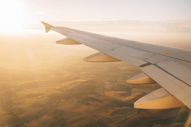 舷窓から地面までの飛行機の翼に太陽が明るく輝いています