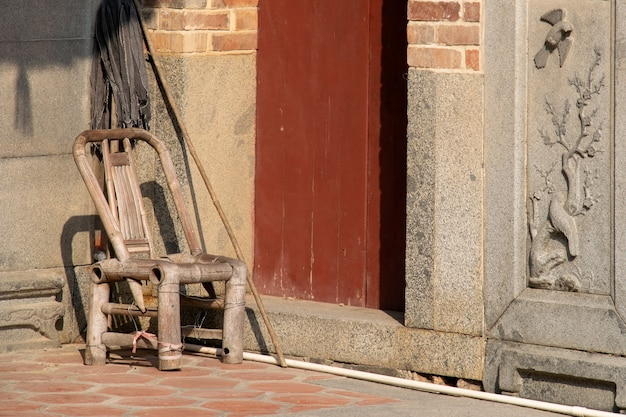 The sun shines on the chair in front of the door of traditional chinese architecture