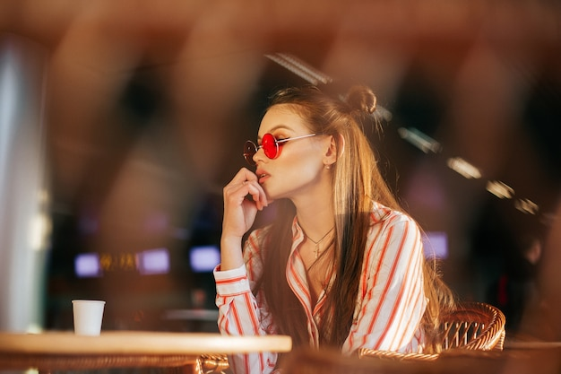 Sun shines over the faces of stunning woman sitting in red sunglasses in the cafe