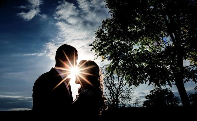 太陽は夕方に古い緑色の木の前にキスする花嫁と新郎の後ろから輝きます