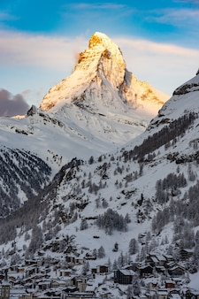 The sun shines on the tip of the matterhorn in the swiss alps just before sunrise in the village of zermatt, switzerland.