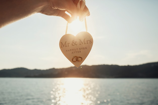 Sun shines over wooden heart with lettering 'mr & mrs happily ever after'  held before sea water
