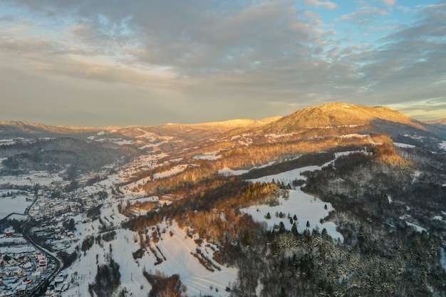 Солнце светит на заснеженных горах над деревней и дорогой в зимний вечер.