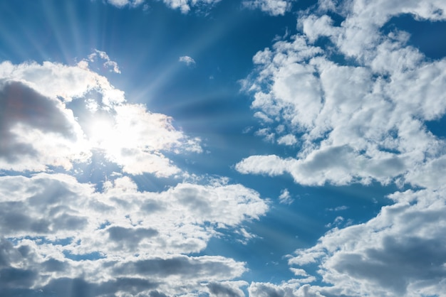 自然の背景として青い空に白い雲を通して輝く太陽