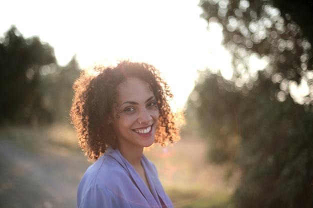 Sole che splende su una donna con i capelli ricci circondata da alberi ed erba