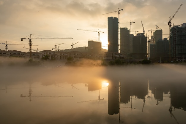 The sun shone on the construction site of the foggy river, which reflected the tall buildings
