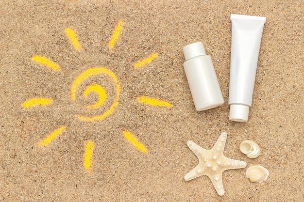 모래, 불가사리 및 흰색 튜브, 선 스크린의 병에 그려진 태양 기호.