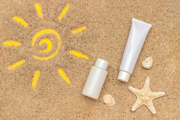 Sun sign drawn on sand, starfish and white tube, bottle of sunscreen.