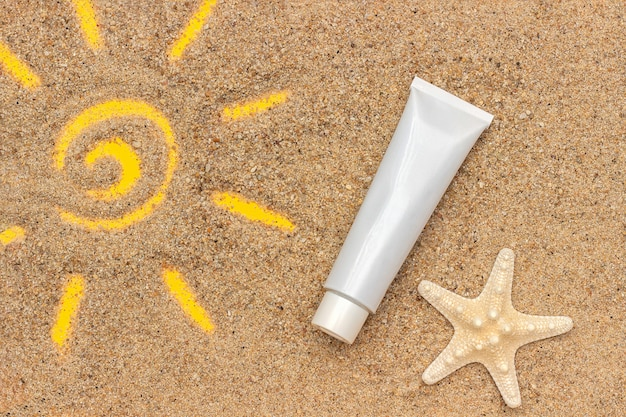 Sun sign drawn on sand, starfish and white tube of sunscreen, closeup. template mockup for your design. creative top view
