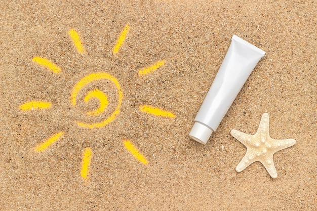 Sun sign drawn on sand, starfish and white tube of sunscreen.