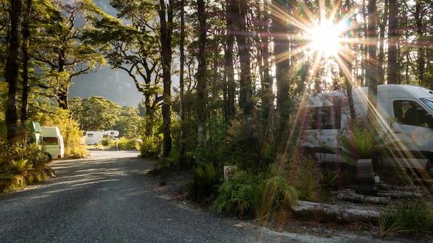 Снимок солнечной звезды кемпинга, расположенного в лесу, с автофургонами на колесах и гравийной дорожкой
