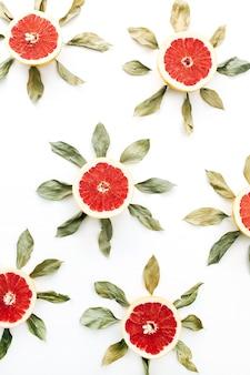 スライスしたグレープフルーツと葉で作った太陽のシンボルパターン。フラットレイ、トップビュー