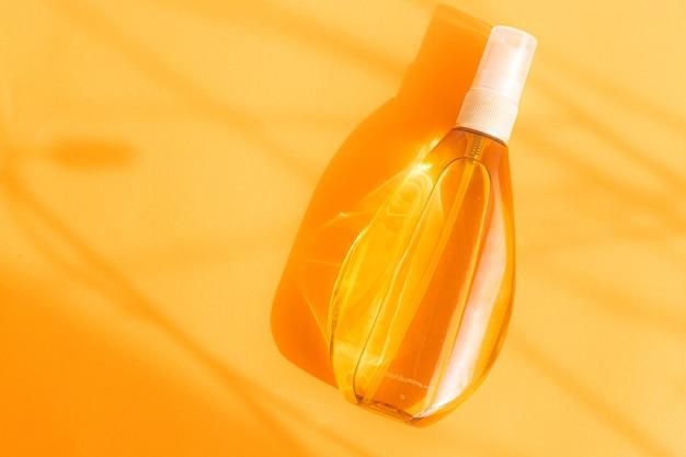 Масло для загара в пластиковой бутылке с распылителем на оранжевом фоне и тени от солнца