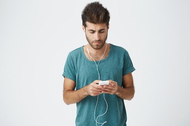 Загорелый парень со стильной стрижкой переписывается с друзьями на белой стене. наушники молодого человека нося, смотря пока отвечающ к сообщению его подруги используя wi-fi