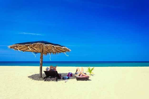 Sun umbrella and sunbed with tourist on the white beach in blue sky day