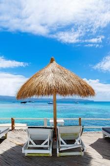 熱帯の海の景色を望むパラソルとビーチベッド。夏休みのコンセプト。
