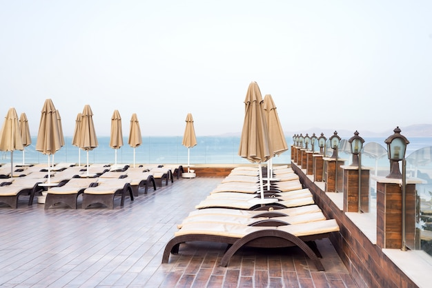 Sun umbrellas beige color and sun beds with view on the sea . holiday vacation concept.