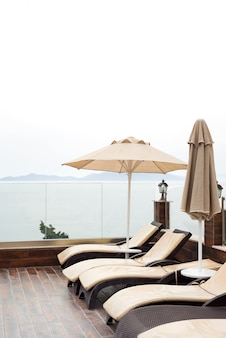 Sun umbrellas beige color and sunbeds near swimming pool with with sea views.