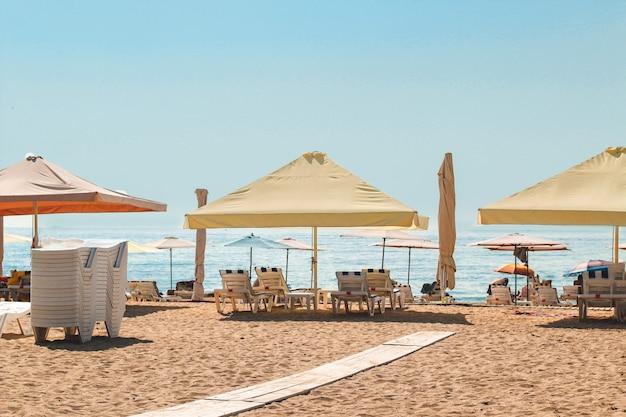 Зонтики на пляже с шезлонгами.