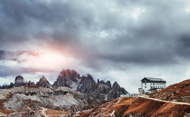 Солнце, которое пробивается сквозь облака, создает красочное зрелище. здание стоит высоко в горах возле кучи скал с туманом.