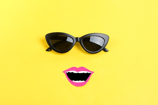 The sun with stylish black sunglasses, smiling mouth on yellow flat lay