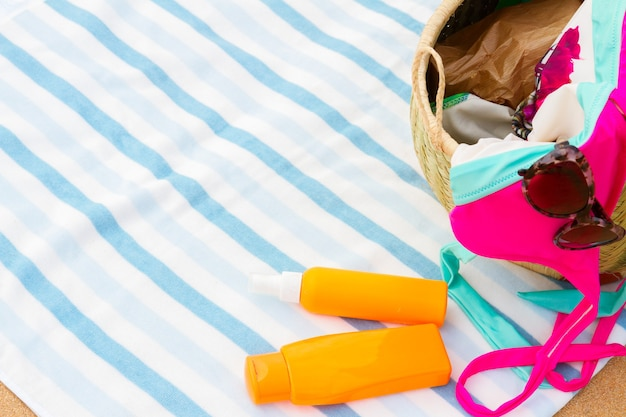 縞模様のビーチタオルのストローバッグで日光浴アクセサリー