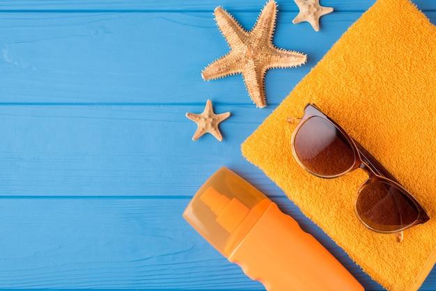 日光浴とリラックスのコンセプト。日焼け止めサングラス黄色いタオルとコピースペースで青い木製の背景に分離されたヒトデの俯瞰図のクローズアップ写真の上に上