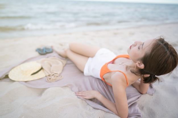 Загорать на пляже, женщина, лежа на песчаной ткани, расслабляясь на летних каникулах.