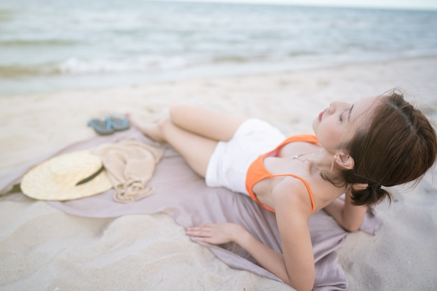 Sunbathing at beach, woman lying on sand fabric relaxing on summer holidays.