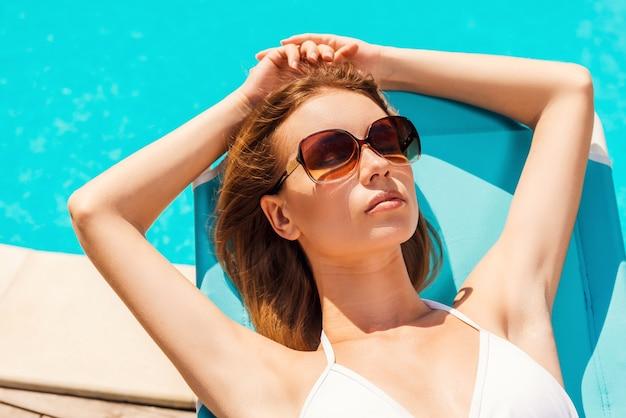 プールサイドで日光浴。プールの近くのデッキチェアでリラックスした白いビキニの美しい若い女性の上面図