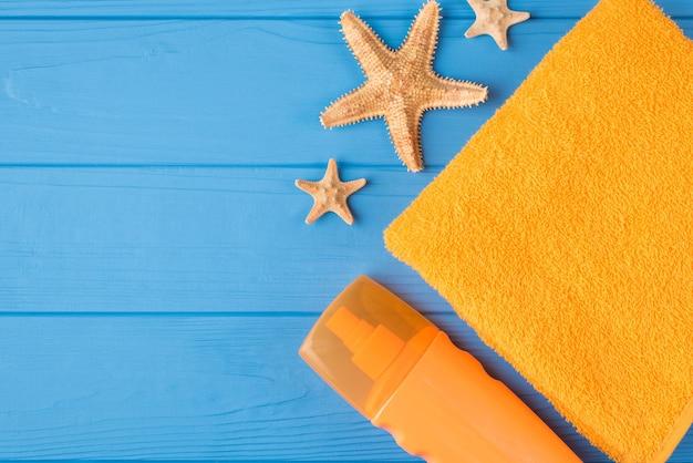 日光浴のコンセプト。コピースペースで青い木製の背景に分離された日焼け止めの黄色いタオルとヒトデの俯瞰図のクローズアップ写真の上の上部