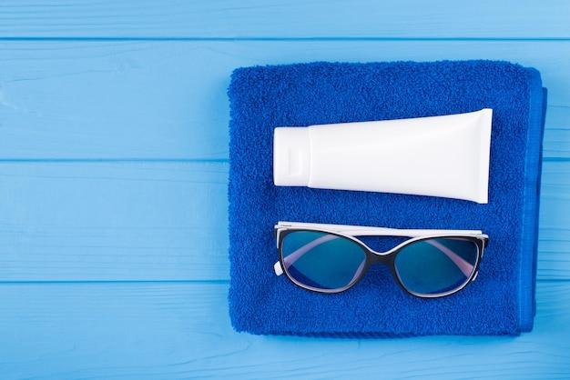 日光浴のコンセプト。コピースペースで青い木製の背景に分離されたタオルサングラスと日焼け止めの俯瞰図のクローズアップ写真の上の上