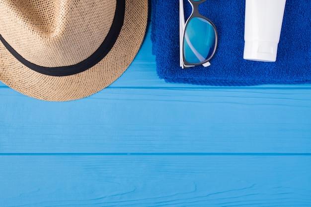 日光浴のコンセプト。上の俯瞰図のクローズアップ写真タオルサングラス日よけ帽とコピースペースで青い木製の背景に分離された日焼け止め