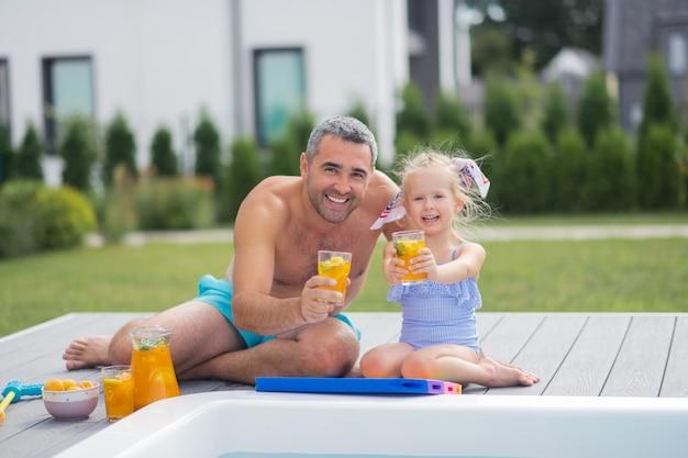 Загорать с папой. милая дочка чувствует себя счастливой, загорая и пьет сок с папой