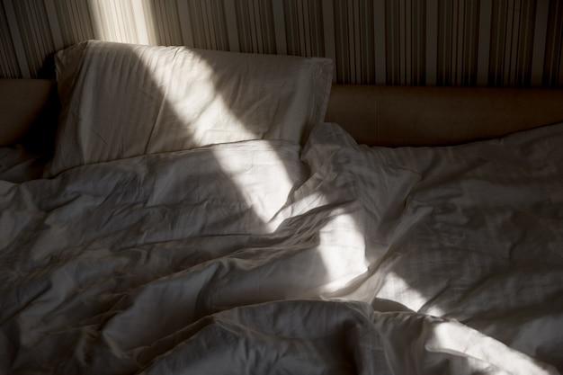 Солнечный луч падает на кровать. солнечные лучи через окно утром. новый день с тёплым солнечным светом.