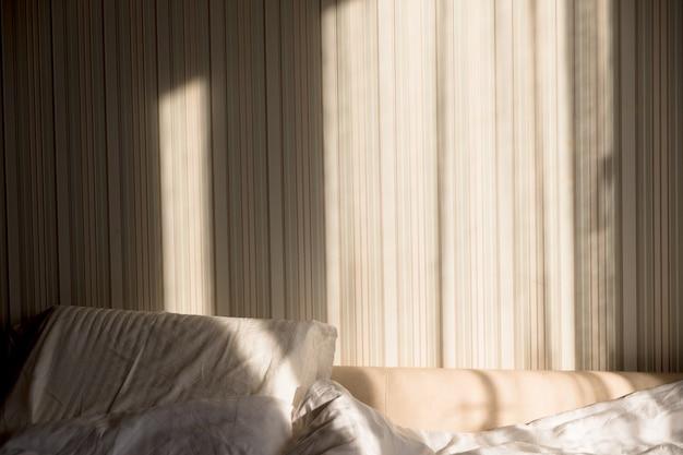 Солнечный луч падает на кровать. солнечные лучи через окно утром. новый день с тёплыми солнечными бликами.