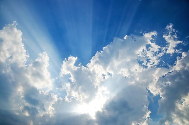 Sunbeam through the haze on blue sky, clouds with sun rays