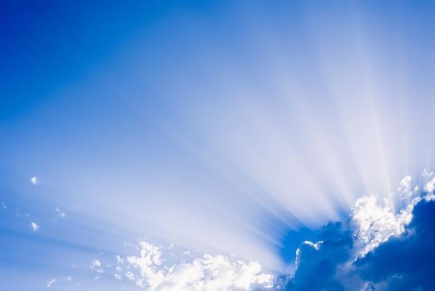 Солнечные лучи, поднимающиеся из большого облака в синем небе в летний день