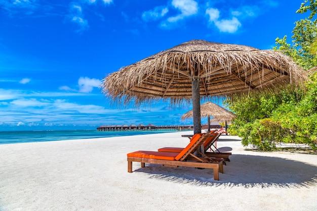 サンベッドとモルディブの熱帯のビーチの傘