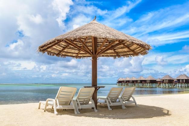 Шезлонг и зонтик на тропическом пляже на мальдивах