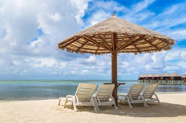 モルディブの熱帯のビーチのサンベッドと傘