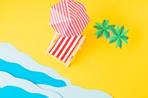 Лежак, игрушечные пальмы, бумажные морские волны. летние каникулы и пляж, концепция морского отдыха