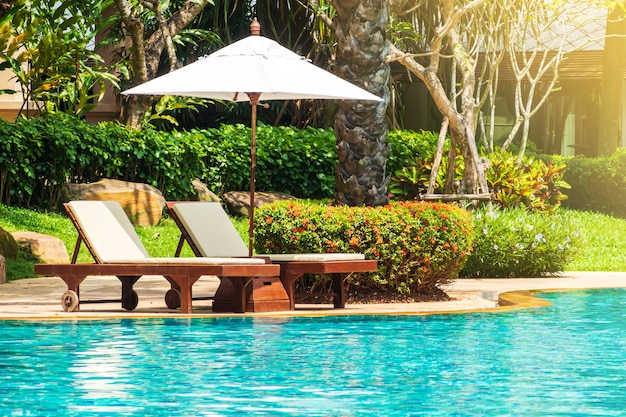 Sunbed with beach umbrella on side of swimming pool. relaxing facility.