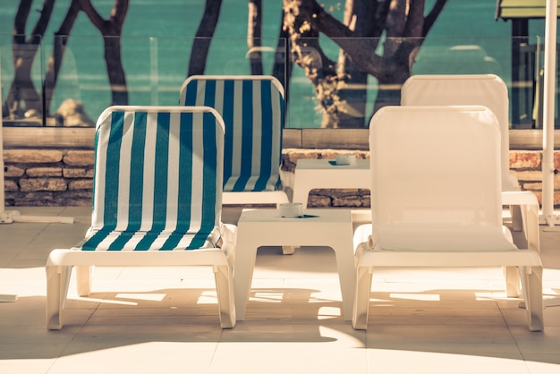 Шезлонги и зонтики у бассейна в солнечный день
