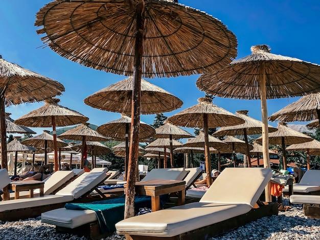 Шезлонги и зонтики на европейском пляже на фоне голубого неба. концепция туризма.