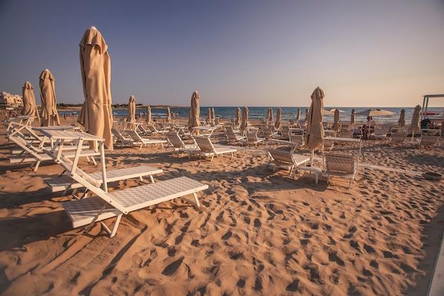 Шезлонги и зонтики на пляже модика на закате